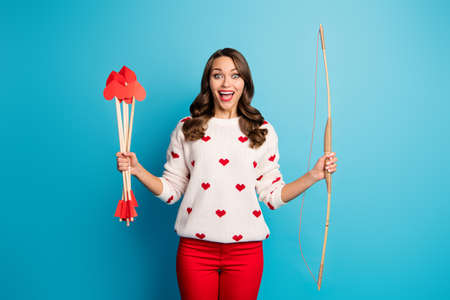 Portrait of her she nice attractive lovely cute girlish funny cheerful cheery glad girl holding in hands amorous arrows great match service isolated on bright vivid shine vibrant blue color background Stock Photo