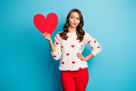 Portrait of her she nice-looking attractive lovely cheerful feminine pensive girl holding in hand heart creating solution congrats isolated on bright vivid shine vibrant blue color background