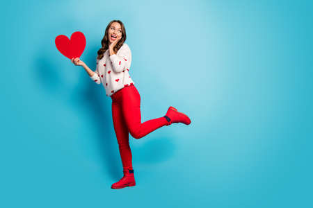 Full length body size view of her she nice attractive lovely cheerful cheery amazed playful girl holding in hand heart having fun isolated on bright vivid shine vibrant blue color background Reklamní fotografie