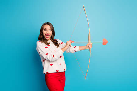 Portrait of her she nice attractive lovely pretty amazed astonished cheerful cheery girl shooting arrow amorous goal isolated on bright vivid shine vibrant blue color background Banco de Imagens - 138268332