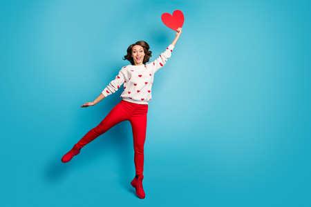 Ganzkörperansicht des netten fröhlichen, fröhlichen, verträumten, lustigen Mädchens, das springt, das Herz fest in der Hand hält und Spaß isoliert auf hell leuchtendem, leuchtend blauem Hintergrund hat Standard-Bild