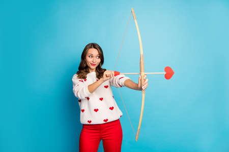 Portrait of her she nice attractive lovely charming winsome lovable cute focused cheerful cheery foxy cunning girl shooting amorous arrow isolated on bright vivid shine vibrant blue color background Banco de Imagens - 138271243