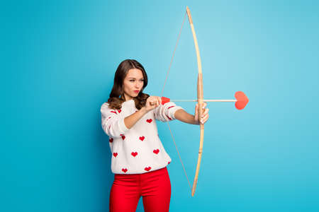 Portrait of her she nice-looking attractive lovely charming pretty cute focused girl shooting sending amorous arrow isolated on bright vivid shine vibrant blue color background