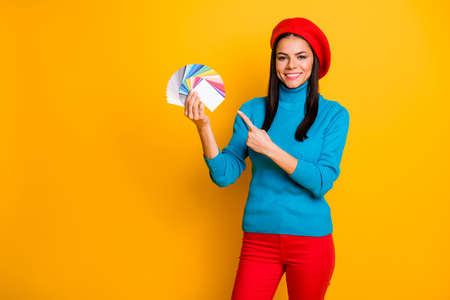 Portrait of her she nice attractive confident cheerful cheery girl designer holding in hand demonstrating different color type decision isolated on bright vivid shine vibrant yellow color background