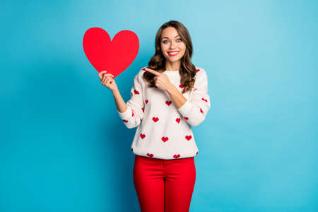 Portrait of her she nice attractive lovely pretty cute glamorous cheerful cheery glad girl holding in hand showing heart congrats isolated on bright vivid shine vibrant blue color background