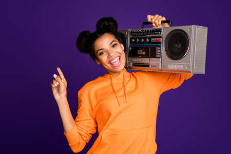 Close-up portrait of her she nice attractive funky cheerful cheery brunette girl in hoody having fun carrying boom box isolated over bright vivid shine vibrant lilac violet purple color background Reklamní fotografie