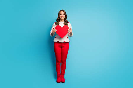Full length body size view of nice attractive lovable cheerful cheery tender dreamy girl wearing festal clothes holding in hand big heart isolated on bright vivid shine vibrant blue color background