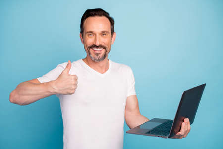 Close-up portrait of nice attractive cheerful cheery guy IT programmer geek holding in hands laptop showing thumbup isolated on bright vivid shine vibrant teal green blue turquoise color background