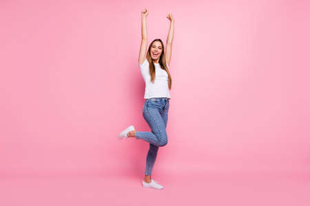 Full length photo of nice lady celebrating mood raise hands fists crazy cheerleader screaming support words wear casual white t-shirt jeans isolated pink color background Фото со стока