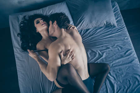 Top above high angle view portrait of his he her she nice attractive adorable perfect fit sporty tender gentle married spouses lying in bed kissing enjoying play game at hotel room house apartment