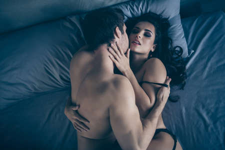 Top above high angle view portrait of nice lovable attractive tender gentle alluring fit perfect couple lying in bed on sheets linen enjoying romance time affair play game Valentine day at hotel house