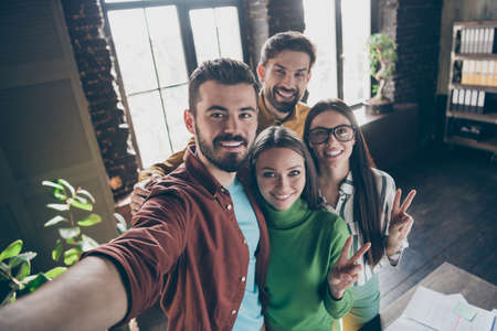 Self-portrait of four nice attractive friendly cheerful cheery professional businesspeople agents brokers showing v-sign having fun at industrial loft interior style workplace workstation office