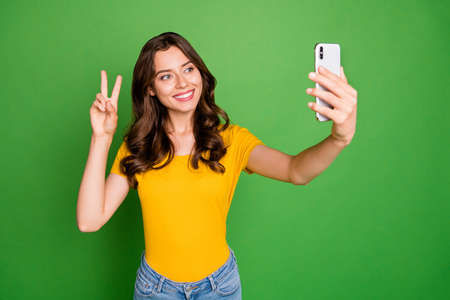 Photo of pretty curly lady holding telephone making selfies showing, v-sign symbol say hello wear casual yellow t-shirt jeans isolated bright green color background