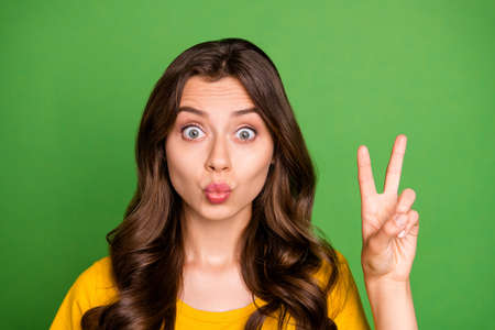 Close-up portrait of her she nice attractive lovely charming coquettish cheery wavy-haired girl showing v-sign sending kiss having fun isolated on bright vivid shine vibrant green color background Stock fotó