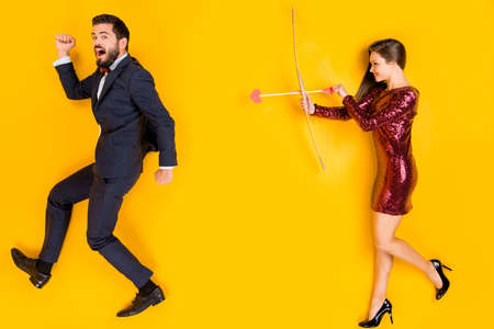 Top above high angle view full size profile side photo two students cunning girl cupid love hunter aim shoot arrow bow guy run wear high-heels tuxedo lay isolated bright shine color background
