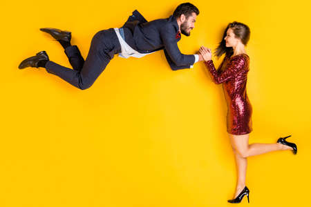 Top above high angle view full body profile side photo of romantic, two passionate people date man air fly girl catch hand wear short red high-heels tux lay isolated shine color background