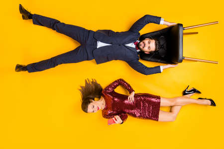Top above high angle full body profile side of charming couple, wedding guests carefree man hold chair up woman type blog post wear red dress tuxedo lay isolated yellow bright color background