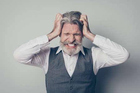 Close up photo of frustrated old executive company owner suffer quarrel loud noise scandal argument feel burnout touch hands head wear stylish vest shirt isolated over grey color background 스톡 콘텐츠