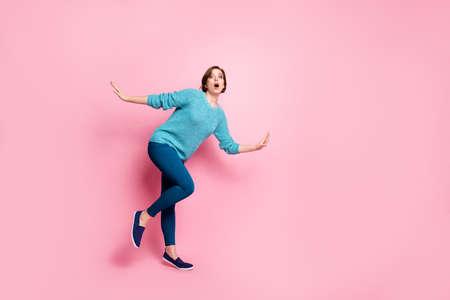 Vista del tamaño del cuerpo de longitud completa de ella ella agradable atractiva encantadora funky preocupada torpe mujer de cabello castaño divirtiéndose engañando fingiendo caer aislado sobre fondo de color rosa pastel