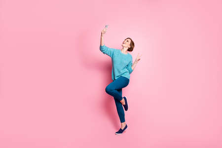 Full length body size view of her she nice attractive lovely cheerful cheery brown-haired girl having fun making taking selfie showing v-sign isolated over pink pastel color background