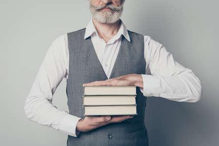 Photo recadrée d'un vieil homme expert tenant des piles de livres qu'il obtient de la bibliothèque porter un gilet de chemise à la mode élégant isolé sur fond de couleur grise