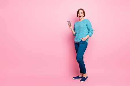 Full length body size view of her she nice attractive lovely cheerful cheery glad brown-haired girl using cell 5g app fast speed web service isolated over pink pastel color background