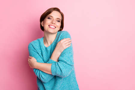Portrait of her she nice-looking attractive lovely charming sweet delighted cheerful cheery brown-haired girl hugging herself isolated over pink pastel color background