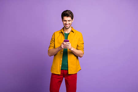 Photo of cheerful toothy beaming man browsing through telephone in red pants isolated violet pastel color background