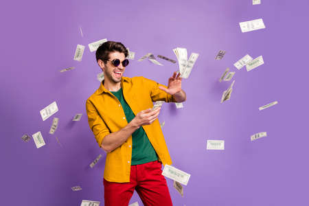 Photo of cheerful excited white trendy man throwing cash away showing his wealthiness smiling toothily in red pants isolated violet color background