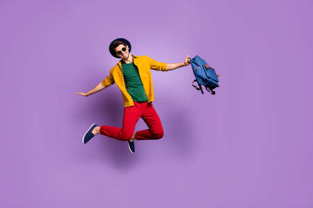 Full size photo of positive guy jump hold hands like bird fly hold blue backpack wear casual modern outfit isolated over purple color background Stock Photo