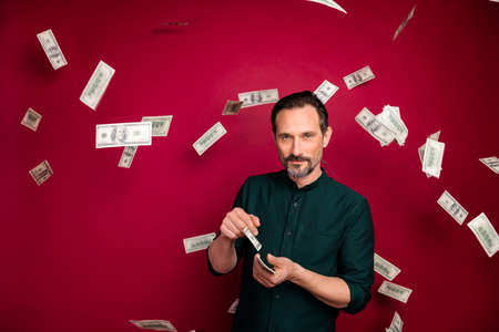 Portrait of his he nice attractive bearded man customer brunette guy holding in hands throwing budget money isolated on bright vivid shine vibrant maroon burgundy marsala red color background 版權商用圖片