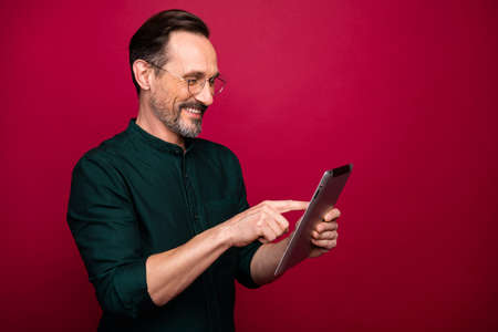 Turned photo of man browsing through modern gadget testing how different applications work on this device isolated red vivid color background