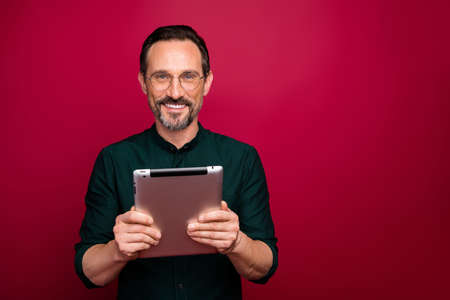 Photo of cheerful attractive man advertising new generation of gadgets standing near empty space smiling toothily isolated red vivid color background Stockfoto