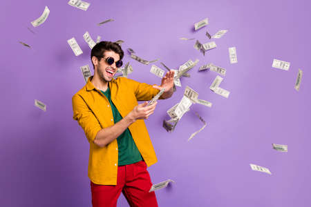 Photo of white cheerful brown haired trendy casual man with bristle throwing cash with crazy emotions on face in red pants yellow shirt isolated violet pastel color background Archivio Fotografico