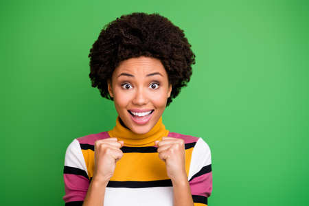 Portrait of amazed cheerful afro american girl hear want expect hope success victory achievement news impressed raise fists scream wear trendy clothes isolated over green color background Stock Photo