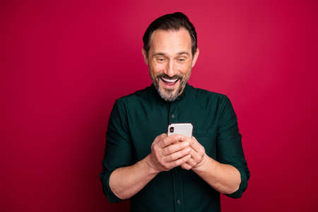 Close-up portrait of his he nice attractive cheerful cheery brunette man using digital gadget got salary sms isolated on bright vivid shine vibrant maroon burgundy marsala red color background