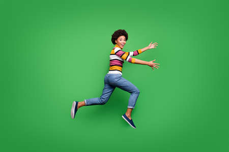 Full size profile side photo of funky crazy afro american girl jump run speedy want hug embrace her best fellow wear bright shine clothing isolated over green color background Standard-Bild