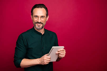 Photo of cheerful positive handsome attractive man holding copybook for writing down interesting information from you isolated vivid color background