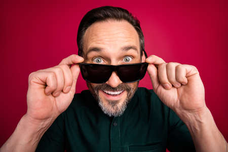 Close up photo of cheerful handsome man looking at you taking his eye glasses away smiling toothily isolated vibrant color background