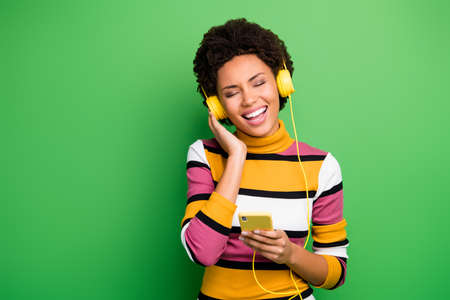 Photo of beautiful dark skin lady hold telephone modern technology earphones listen new popular songs eyes closed wear casual striped jumper isolated green color background