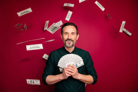 Close-up portrait of nice cheerful cheery bearded man holding in hand freelance interest rate currency exchange isolated on bright vivid shine vibrant maroon burgundy marsala red color background 版權商用圖片