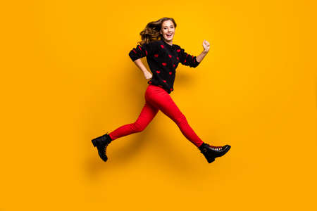 Full length profile photo of pretty lady jumping up high speed rushing low prices shopping wear hearts pattern sweater red trousers boots isolated yellow color background