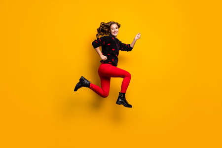 Full length profile photo of funny lady jump up high speed rushing low prices addicted shopper wear hearts pattern sweater red trousers footwear isolated yellow color background