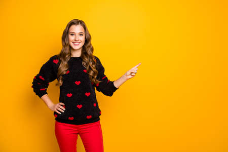 Photo of funny pretty lady indicating finger empty space advising amazing low shopping season prices wear hearts pattern pullover red pants isolated yellow color background Banco de Imagens