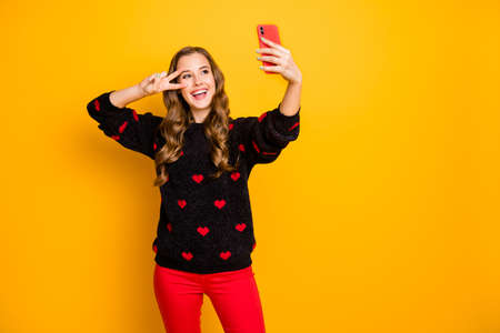 Photo of funny pretty lady hold telephone hands taking funny energetic selfies showing v-sign near eye wear hearts pattern pullover red pants isolated yellow color background