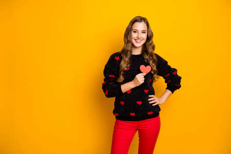 Photo of pretty curly lady amour holding little paper heart hear chest symbolizing cardiology health care wear hearts pattern sweater red trousers isolated yellow color background
