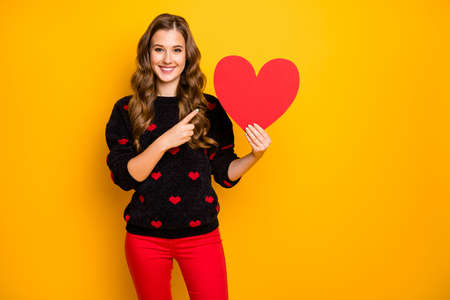 Photo of amazing curly lady amour hold big paper heart indicating finger creative idea date invitation wear hearts pattern sweater red pants isolated yellow color background