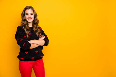 Photo of pretty curly long hairdo lady self-confidently crossing arms good positive mood wear warm black red hearts pattern sweater trousers isolated yellow color background