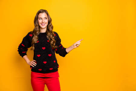 Its sale oclock. Photo of funny lady indicating finger empty space advising amazing low shopping prices wear hearts pattern pullover red pants isolated yellow color background Banco de Imagens