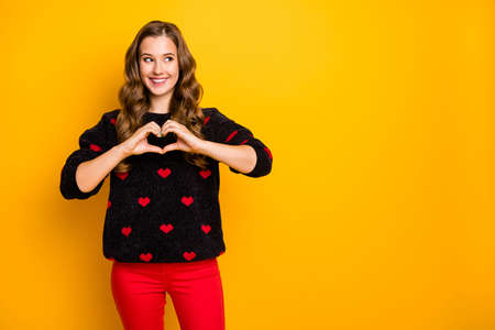 Photo of funny wavy lady look empty space inviting boyfriend romantic date making arms heart figure wear black red hearts pattern sweater trousers isolated yellow color background